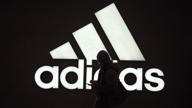 girl walks past a light box of adidas shop. the adidas is expected to see a global sales increase by 5% to 8% in 2019, while maintaining two-digit... - adidas stock videos & royalty-free footage