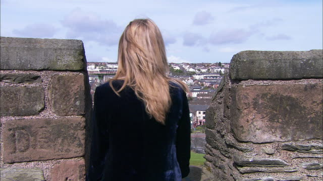 girl walks to turrets, looks through at derry houses below, from magazine st, northern ireland - derry northern ireland stock videos & royalty-free footage