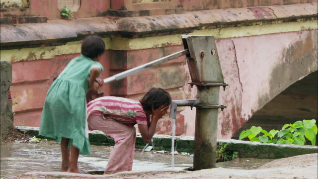 a girl washes her face in water as her young sister operates the hand pump. available in hd. - vattenpump bildbanksvideor och videomaterial från bakom kulisserna