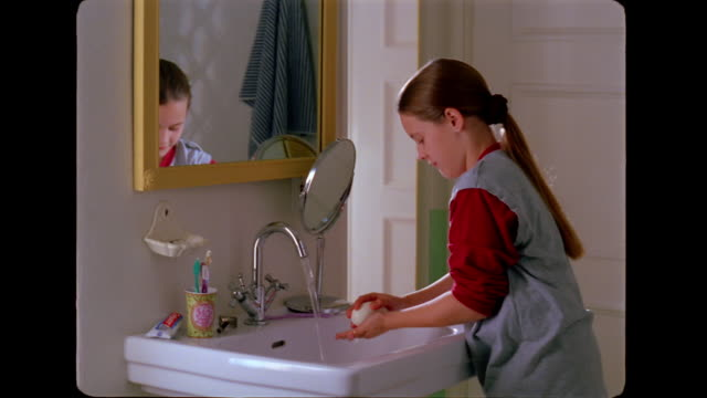 A girl washes her hands and splashes water on her face.