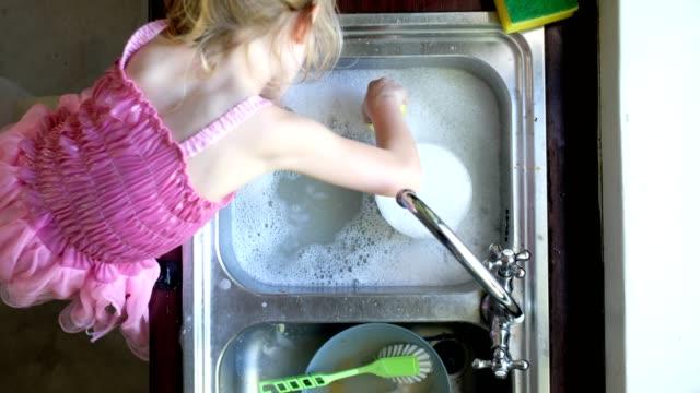 vídeos de stock, filmes e b-roll de menina lava os pratos e se diverte - lavando louça