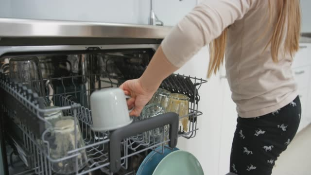 girl washing a cup and placing it into the dishwasher - lavastoviglie video stock e b–roll