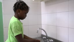Girl washing hands in kindergarten bathroom