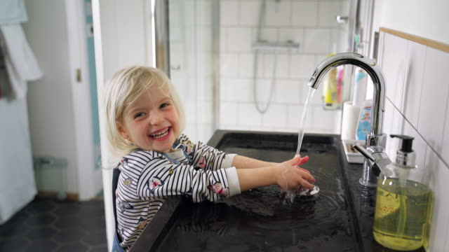 girl washing her hands in the sink and splashing water - east sussex stock videos & royalty-free footage