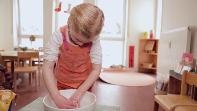 MS Girl washing her hands with brush in bowl / Potsdam, Brandenburg, Germany