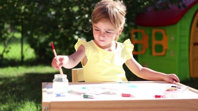彼女のペイントブラシを洗う女の子 - 美術工芸品点の映像素材/bロール