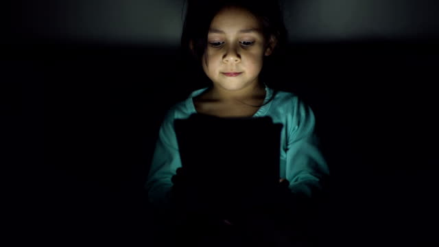 A girl watches cartoons in the tablet late in the evening