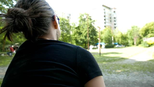 flickan tittar barnen leker i parken - endast en tonårsflicka bildbanksvideor och videomaterial från bakom kulisserna