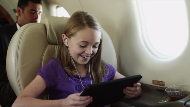 MS Girl (10-11) watching movie on digital tablet in airplane / Spanish Fork, Utah, USA