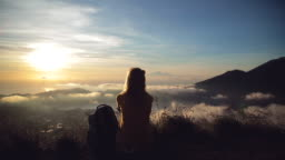 Girl watching the sunrise from mount Batur, Bali - Indonesia.