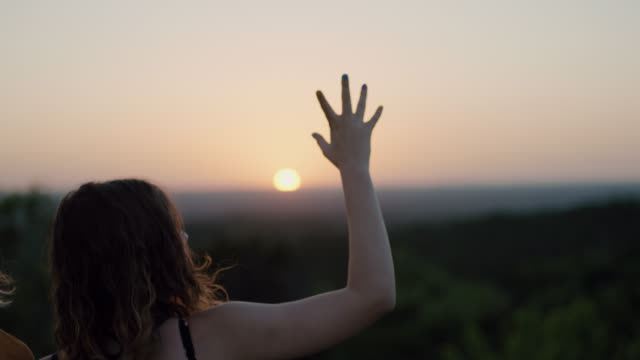 MS SLO MO. Girl waves hand in air and looks out over open valley with friends at magic hour.
