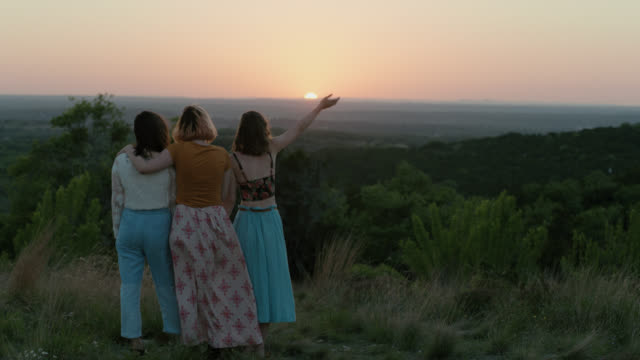 WS SLO MO. Girl waves hand in air standing on lush green mountainside with friends at sunset.