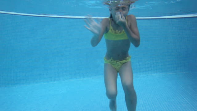 Girl waving and holding nose underwater
