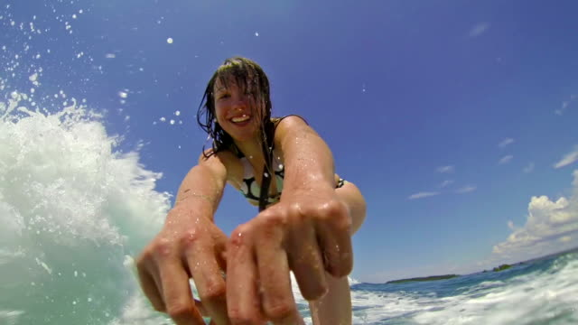 Girl waving and smiling into the camera while surfing