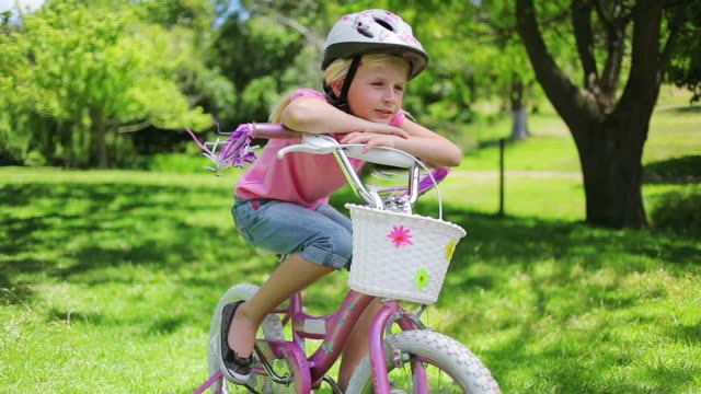 a girl sits on a bike while leaning on the handlebars as its tassels blow in the wind - tassel stock videos & royalty-free footage