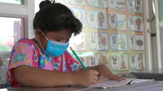 una ragazza che indossa una maschera che fa i compiti in una scuola - riapertura delle scuole video stock e b–roll