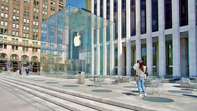 girl wearing a mask takes a picture of closed apple store during coronavirus. - big tech stock videos & royalty-free footage