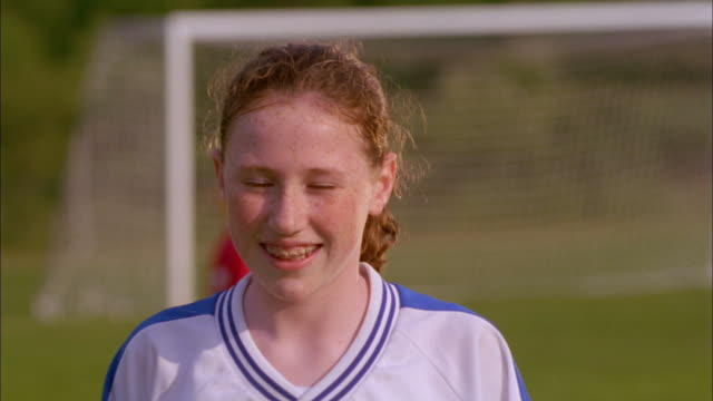 a girl wearing braces and a soccer jersey smiles and laughs. - freckle stock videos & royalty-free footage