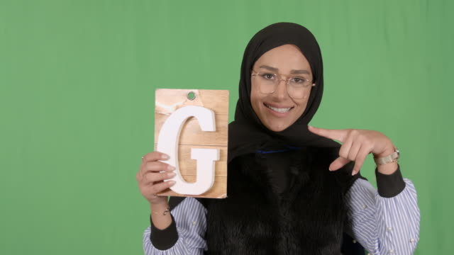 girl wearing hijab holding letter g - modest clothing stock videos & royalty-free footage