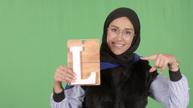 girl wearing hijab holding letter l - modest clothing stock videos & royalty-free footage