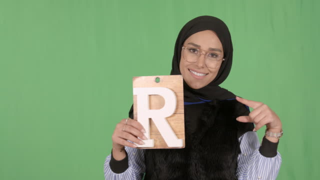 girl wearing hijab holding letter r - modest clothing stock videos & royalty-free footage