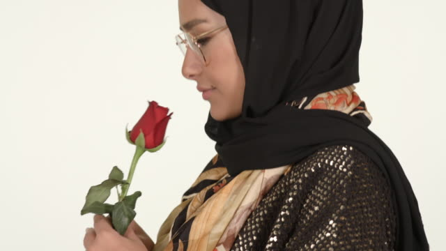 girl wearing hijab holding red rose - modest clothing stock videos & royalty-free footage