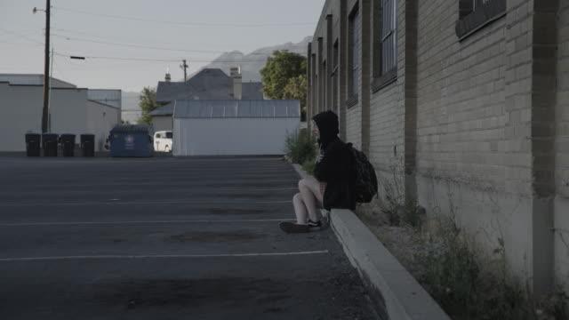 girl wearing hooded sweatshirt sitting on curb in empty parking lot / provo, utah, united states - runaway stock videos & royalty-free footage