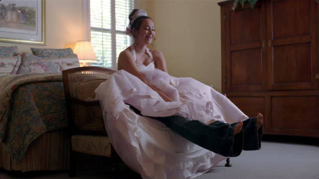 girl wearing jeans underneath quinceanera dress / sitting down onto love seat in bedroom - 少女のみ点の映像素材/bロール