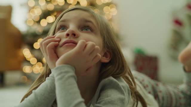 stockvideo's en b-roll-footage met girl wearing pajamas laying on floor near christmas tree looking up / vineyard, utah, united states - concentratie