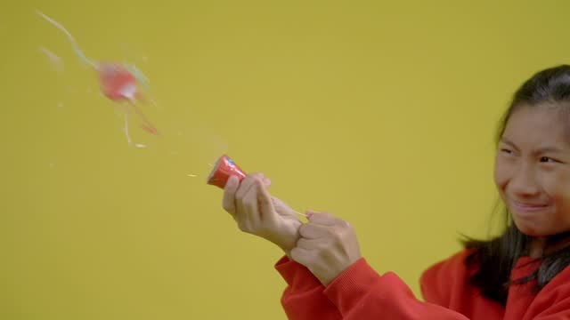 girl wearing red sweater playing fire crackers with yellow background. slow motion. - firework explosive material stock videos & royalty-free footage