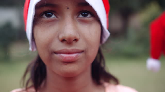 girl wearing santa hat looking at camera and smiling - weihnachtsmütze stock-videos und b-roll-filmmaterial