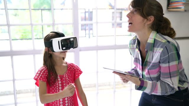 girl wearing virtual reality simulator by teacher - maestra video stock e b–roll