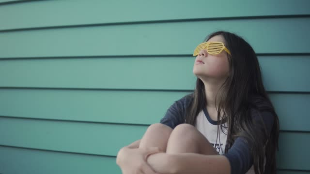 a girl wearing yellow novelty glasses lost in her thoughts - innocenza video stock e b–roll