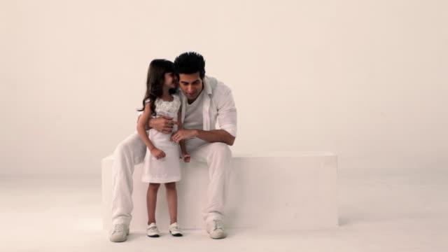 girl whispering into her father's ear  - スタジオ撮影点の映像素材/bロール