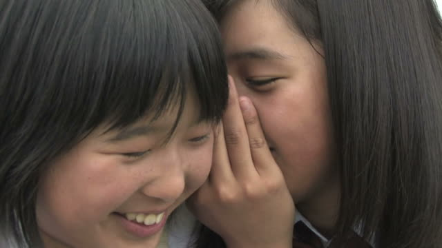cu girl whispering into her friend's ear - japanese school uniform stock videos & royalty-free footage