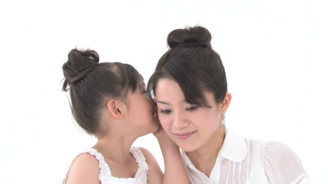 Girl whispering into her mother's ear and mother whispering into grandmother's ear