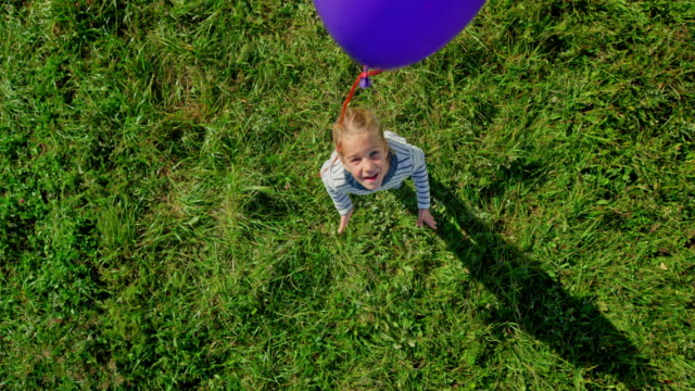 slo mo cs girl with a blonde pony tail releasing a balloon into the sky in the sunny meadow - zoom out video stock e b–roll