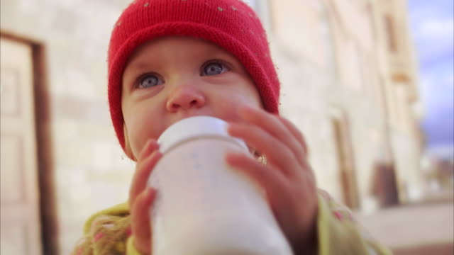 stockvideo's en b-roll-footage met a girl with a feeding bottle sweden. - zuigfles