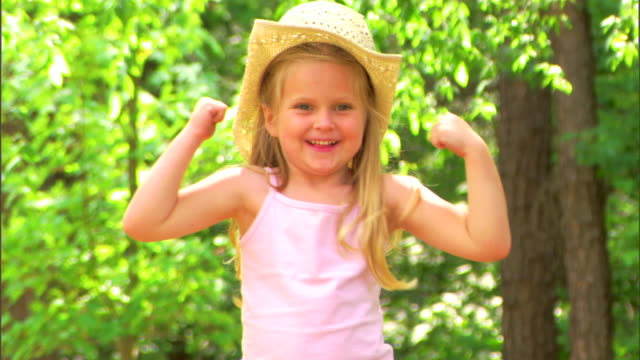 Girl with a straw hat flexing muscles