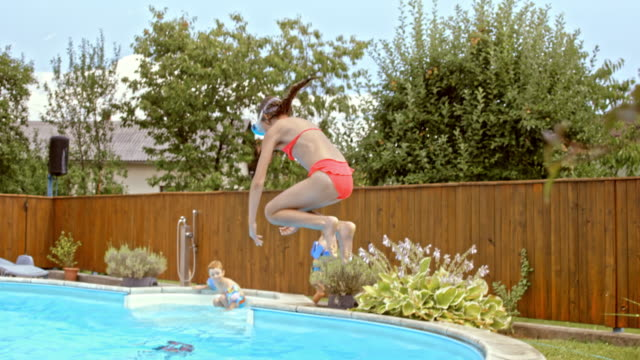 slo mo girl with a swimming mask jumping into the pool - bikini stock videos & royalty-free footage