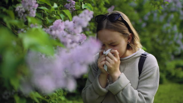 girl with allergy sneezing and cleaning nose in park near blooming flowers in springtime - allergy stock videos & royalty-free footage
