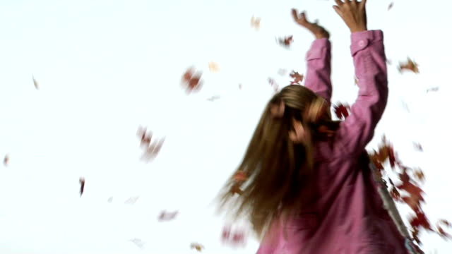 Girl with arms up and leaves falling