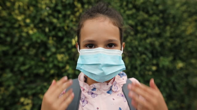 girl with backpack putting on protective face mask - applying stock videos & royalty-free footage