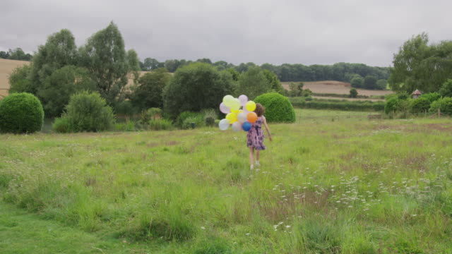 girl with balloons in field - floral pattern stock videos & royalty-free footage