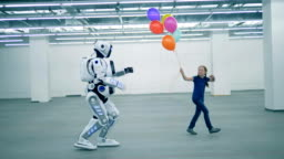 A girl with balloons is dancing and a manlike robot is coming towards her