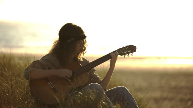 girl with bandana, playing acoustic guitar, john lennon glasses style, sunset, sunshine, beach - teenage girls video stock e b–roll