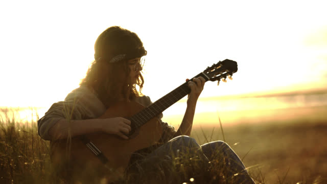 girl with bandana, playing acoustic guitar, John Lennon glasses style, sunset, sunshine, beach