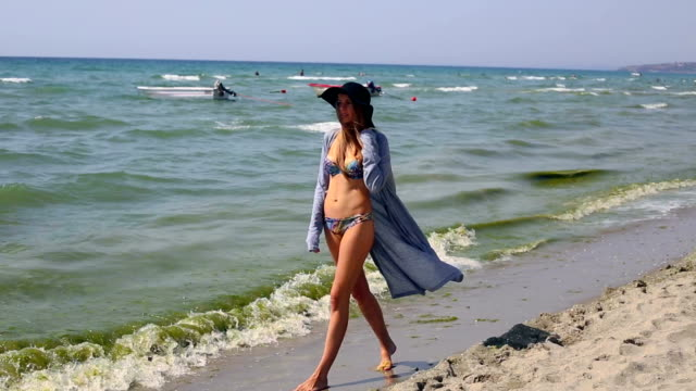 girl with black hat and pareo is walking on beach - sarong stock videos and b-roll footage