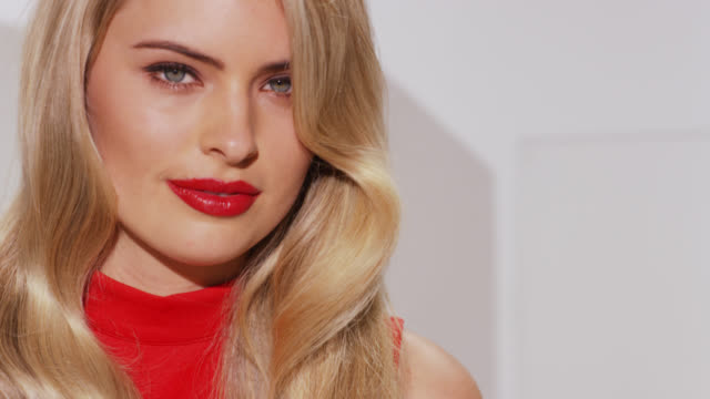 vídeos de stock e filmes b-roll de girl with blonde wavy hair and bold red lipstic looks to camera - lábio
