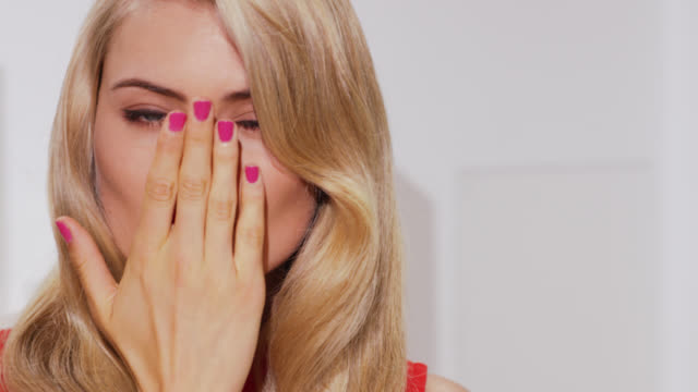 Girl with blonde wavy hair and bold red lipstic shows blows kiss to camera